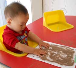 baby doing art in red table